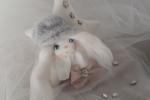 Bambolina con cuffietta pelosa e fiocco al collo