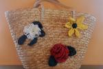 Borsa di paglia decorata con fiori realizzati a uncinetto