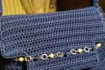 Borsa blu in cordino, con catenella sulla patta.