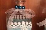 Bottiglia decorata con nastro azzurro e pizzo bianco