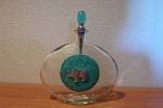 Bottiglia in vetro decorata con placca in ceramica