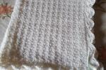 Copertina in lana bianca per bebè con fiocchetti celesti