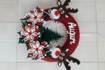 Corona natalizia con renne e scritta auguri, sui toni del rosso, verde, bianco