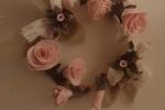 Ghirlanda dai toni delicati del rosa realizzata con nastri in pizzo