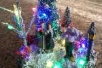 Ambientazione invernale con piccoli personaggi su muschio e neve