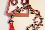 Parure di collana e orecchini nei toni del rosso, nero, dorato e bronzo.