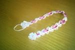 Portaciuccio realizzato a uncinetto in cotone bianco con fiocco rosa