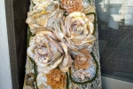 Tegola antica decorata con rose lavorate con il gesso e con bucce dei pistacchi